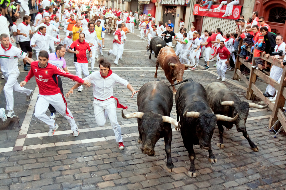 Photo of People Running in the Street With Bulls